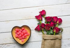 Red heart shaped candy bowl and rose. Red roses placed on a bowl of red heart-shaped candy on a white vintage wooden background, with a copy space for the royalty free stock images