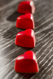 Red heart-shaped candy laid out in a row on the table. Postcard or background on Valentine`s Day Stock Photos