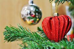 Red heart shaped Christmas decoration on Christmas tree stock photo