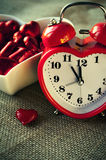 Red heart shaped clock with sweet chocolates Stock Images