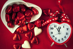 Red heart shaped clock with sweet chocolates. Close up. Time for love Royalty Free Stock Photos