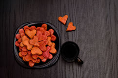 Red heart-shaped cookies on a black plate, coffee mug , Valentine's Day Royalty Free Stock Images