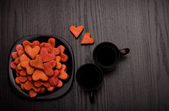Red heart-shaped cookies on a black plate, two mugs of coffee, top view Royalty Free Stock Photography