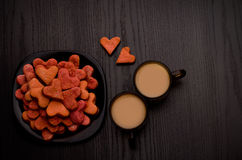 Red heart-shaped cookies and two mugs of coffee with milk on a black table. Valentine's Day Stock Photo