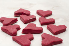 Red heart-shaped cookies on a white table closeup, baking for Valentine's Day Stock Image