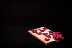 Red heart-shaped cookies on a wooden plank, baking the day of Valentine's Royalty Free Stock Images