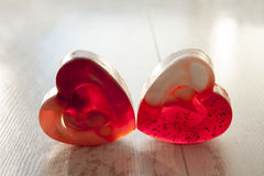 Red heart shaped couple soup. Red translucent heart shaped handmade couple soap on gray wooden background Stock Photography