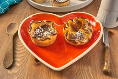 Red heart-shaped dish with pastries for Valentine`s Day. stock image