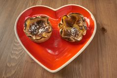 Red heart-shaped dish with pastries for Valentine`s Day. royalty free stock images