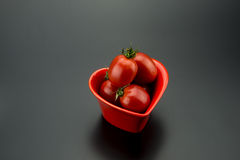 Red heart-shaped dish and small tomatoes Royalty Free Stock Images