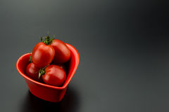 Red heart-shaped dish and small tomatoes Stock Photos