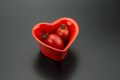 Red heart-shaped dish and small tomatoes Royalty Free Stock Photography