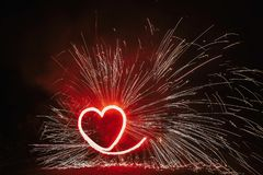 Red heart shaped firework with sparkles on black background in n royalty free stock photos