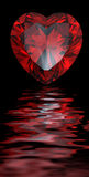 Red heart shaped garnet reflected on water Stock Photo