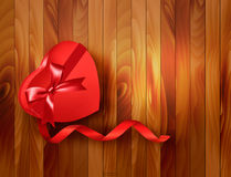 Red heart-shaped gift box with ribbon on wooden ba Stock Image