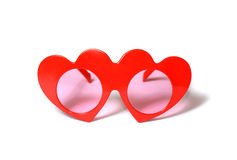 Red heart-shaped glasses on white Royalty Free Stock Images