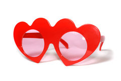 Red heart-shaped glasses on white Stock Photography