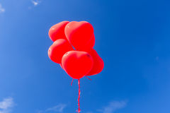 Red heart shaped helium balloons flying in the sky Stock Photo