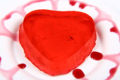 Red heart shaped jello. On a plate decorated with fruity custard Royalty Free Stock Images