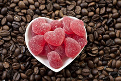 Red heart shaped jelly sweets and coffee beans Royalty Free Stock Images
