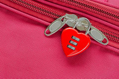 Red heart shaped lock with code locking fabric suitcase luggage. Closeup top view of red heart shaped lock with code locking fabric suitcase luggage stock image
