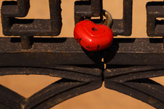 Red heart-shaped lock hanging on metal fence Royalty Free Stock Photos