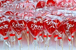 Red heart shaped lollipop on a market stand Stock Photo