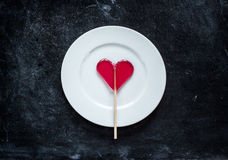 Red heart shaped lollipop on plate - valentines day Royalty Free Stock Images