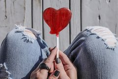 Red heart shaped lollipop in a trendy fashionable woman`s hands, top view. Stock Image