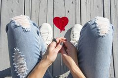 Red  heart shaped lollipop in a trendy fashionable woman hand, top view. Stock Image
