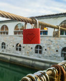 Red heart shaped padlock hanging from string. Crossing bridge of river Royalty Free Stock Photos