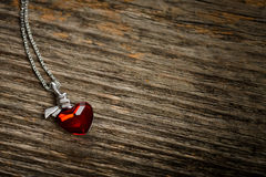 Red heart-shaped pendant. On wood texture stock images
