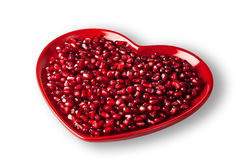 Red heart shaped plate full of delicious ripe juicy pomegranate seeds. Royalty Free Stock Images