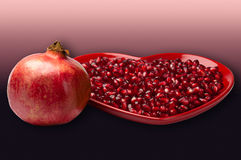 Red heart shaped plate full of delicious ripe juicy pomegranate seeds whole fruit gradient background Royalty Free Stock Images