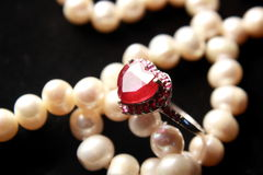 Red Heart. Shaped ruby ring with soft blurred pearl background Royalty Free Stock Photo