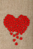 Red heart shaped sewing buttons on canvas. Red heart shaped handmade wooden sewing buttons form broken heart on linen canvas with copy space left, elevated top Royalty Free Stock Photo