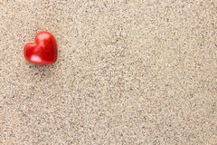 Red heart shaped stone on sand surface. With copy-space Royalty Free Stock Images