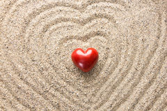 Red heart shaped stone on sand surface Stock Photos