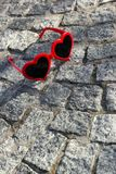 Red, heart shaped sunglasses on a floor on a street Stock Image