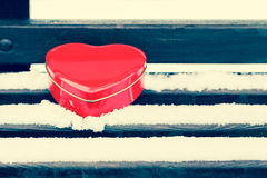 Red heart shaped tin box on a bench covered with snow Royalty Free Stock Images