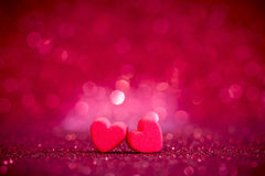 Red Heart shapes on abstract light glitter background in love co Stock Image