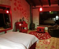 PRIVATE COUPLES SUITE AT LUNA RUNTUN, BANOS ECUADOR. Red heart shapes painted on the wall along with pink and white rose petals on the floor welcome guests. A Royalty Free Stock Photo