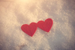 Red heart shapes on snow Stock Images