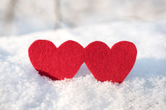 Red heart shapes on snow Stock Image