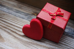 Red heart and small gift box with a bow on a wooden background. Royalty Free Stock Image