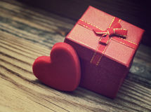 Red heart and small gift box with a bow on a wooden background. Stock Image