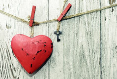 Red heart and small metal key on wooden cloth pegs on the clothesline Stock Photos
