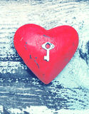 Red heart and small metal key on a wooden old background. Stock Photo