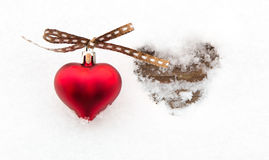 Red heart on snow next to melted heart shape Stock Photography
