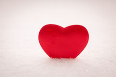 Red heart on snow Stock Images